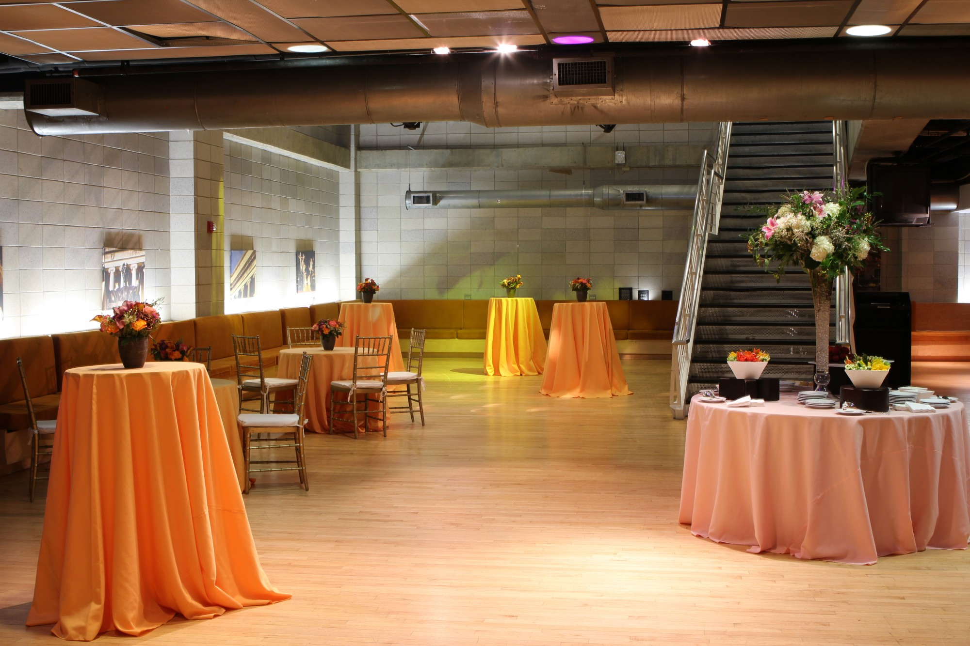 A large, open space with wooden floors and concrete walls. Cocktail tables are set-up around the room, draped with orange tablecloths. A large staircase leads to an upper level.