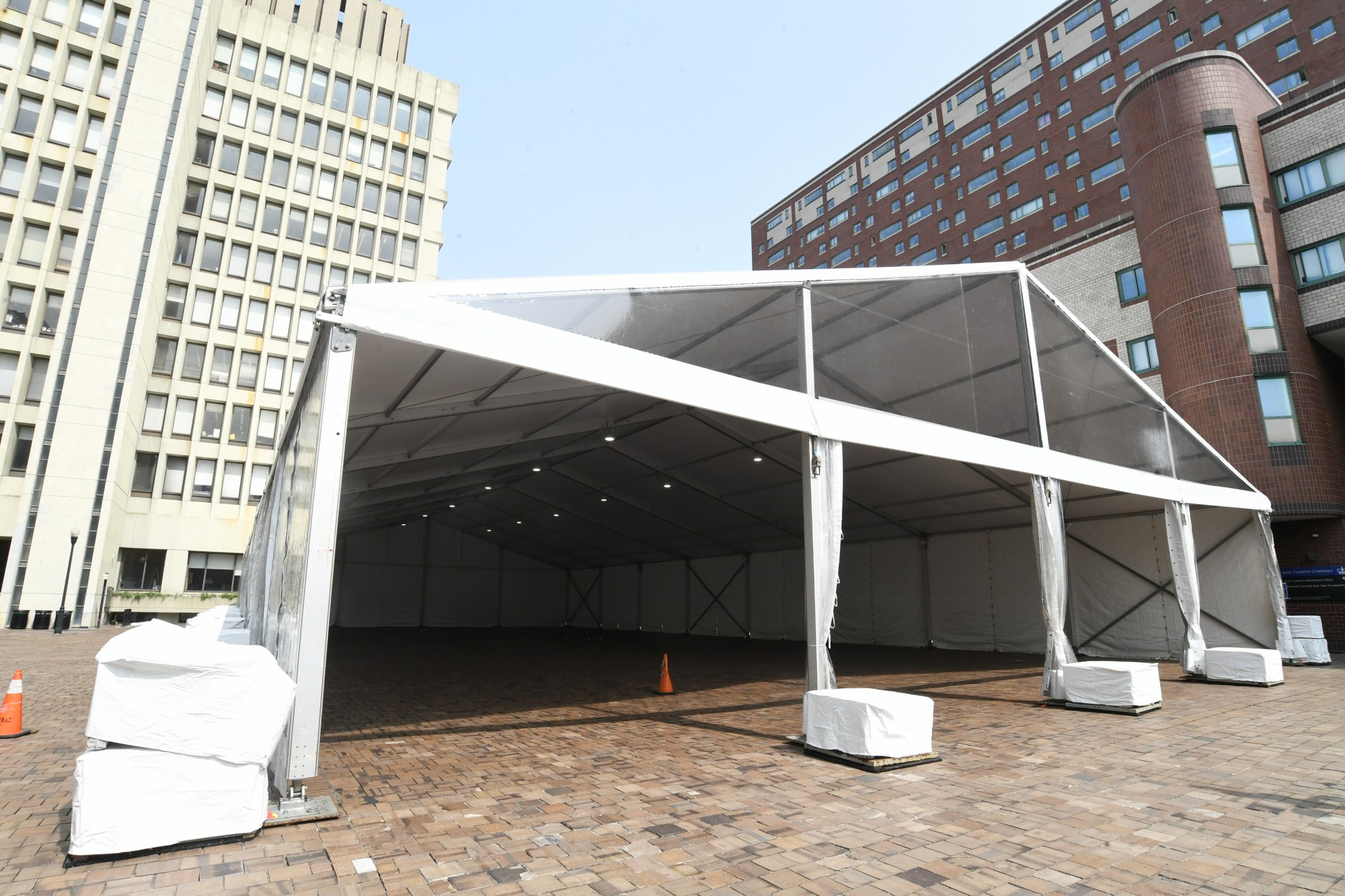 An open air tent erected on a brick patio outside of two University buildings.