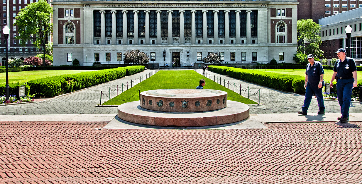 Two stacked concrete circle on a brick walkway. In the distance, a three separate lawns sit in front of a grand columned building.