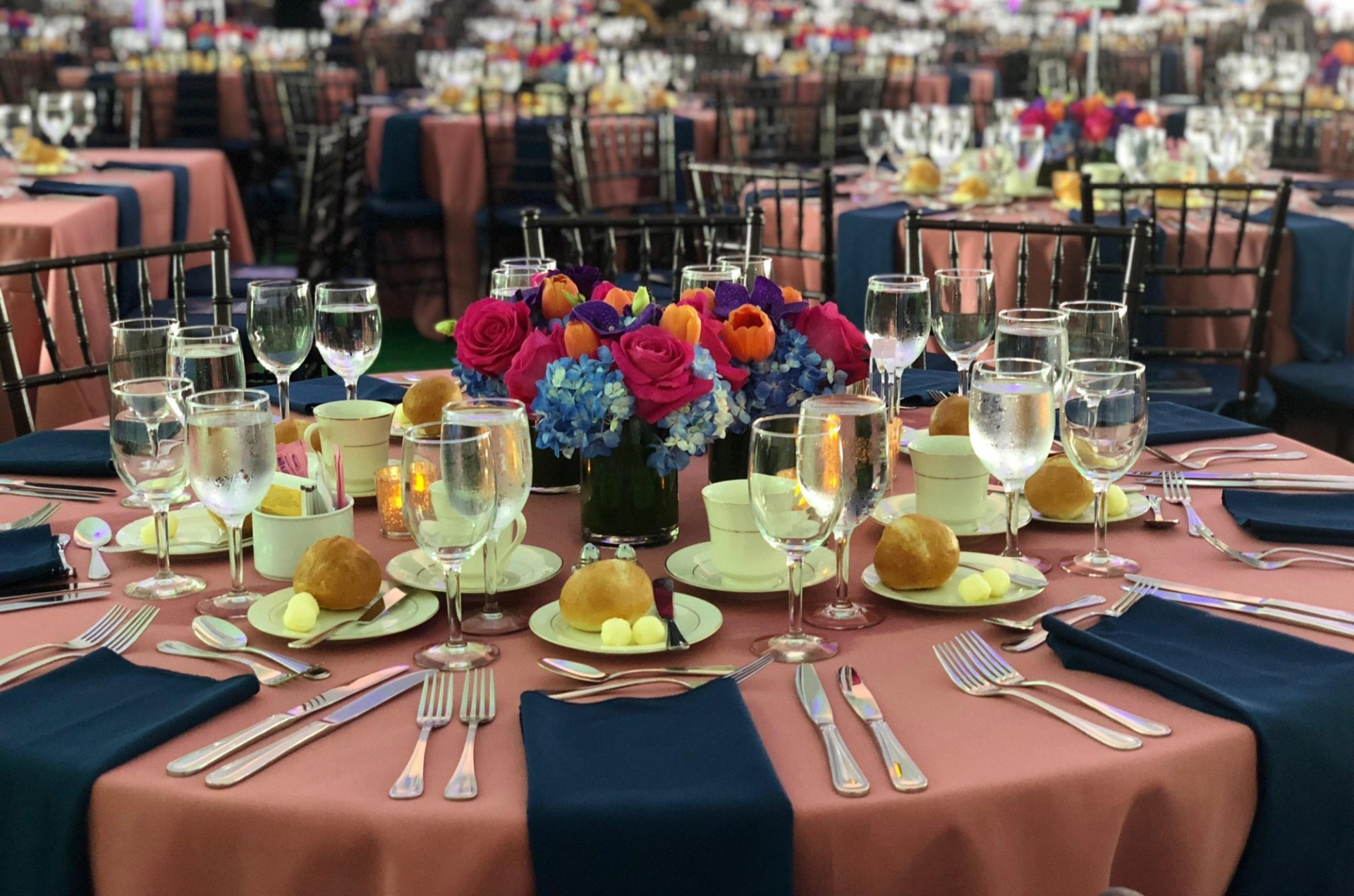 A banquet round is dressed with a pink tablecloth and navy blue napkins. Dinner rolls are placed at every place setting. At the center of the table is a fresh floral arrangement.