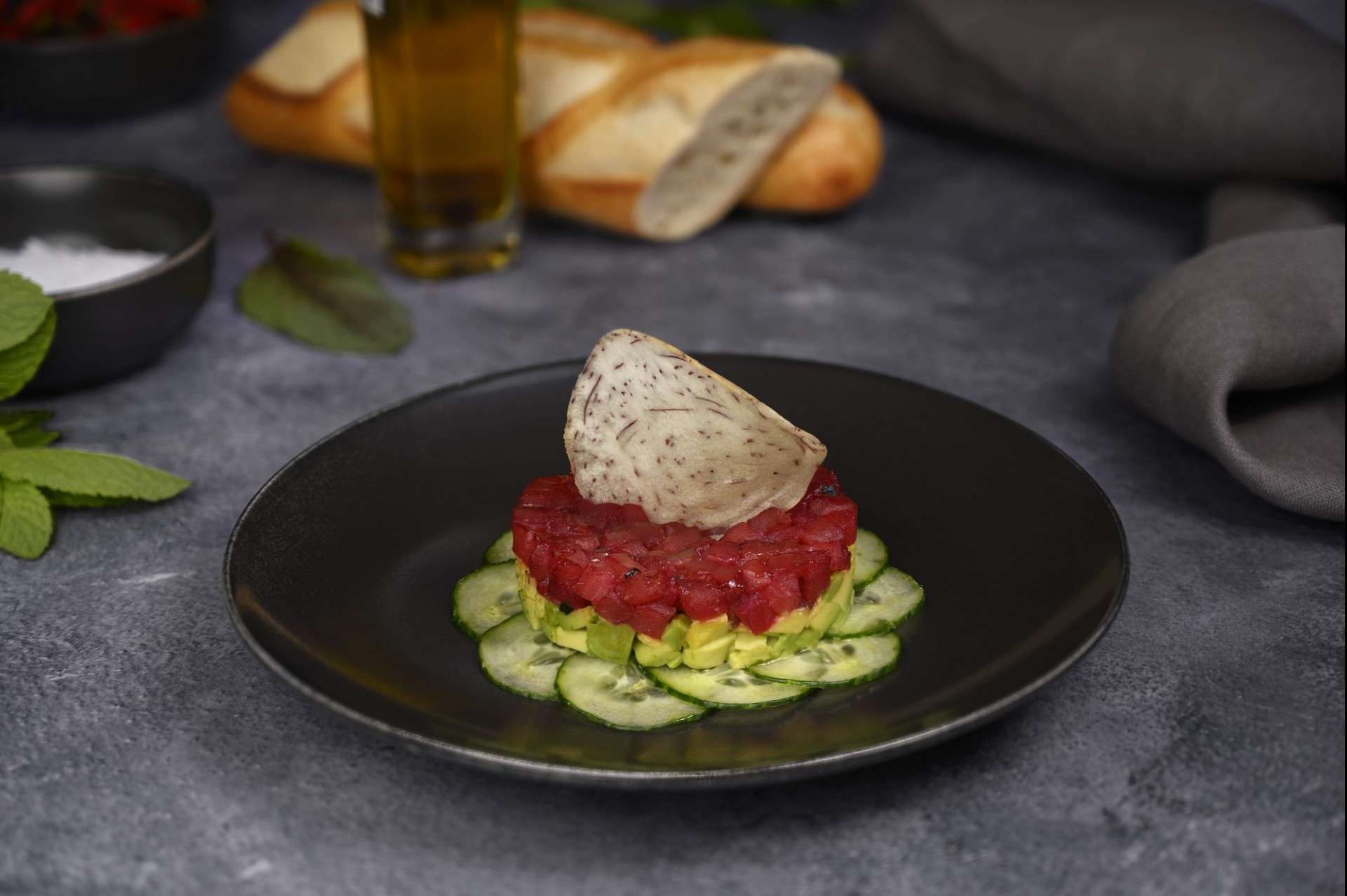 Tuna tartar topped with a taro chip sits on a bed of thinly sliced cucumber