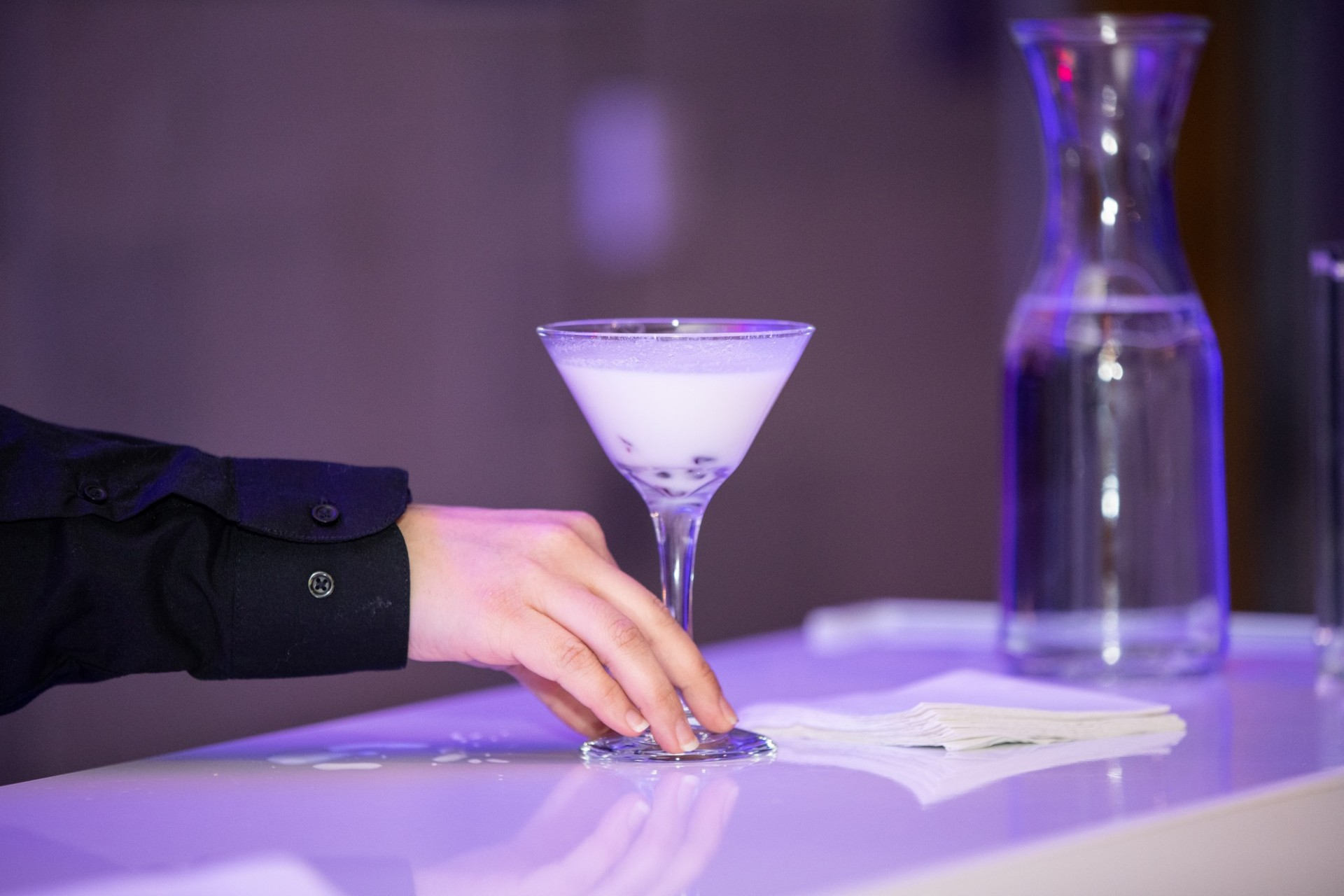 A person serves a cocktail
