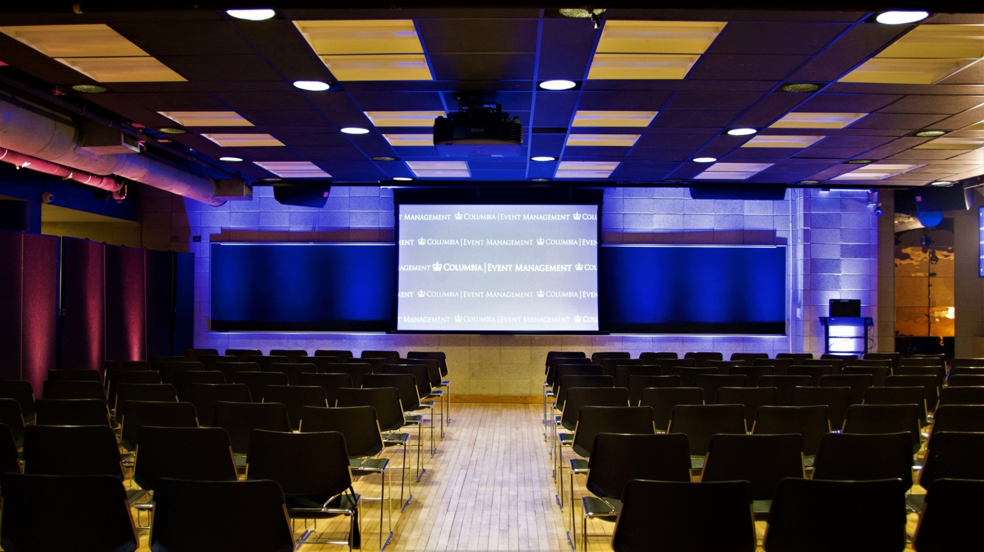 Rows of black chairs face a projector screen mounted on a stone wall.