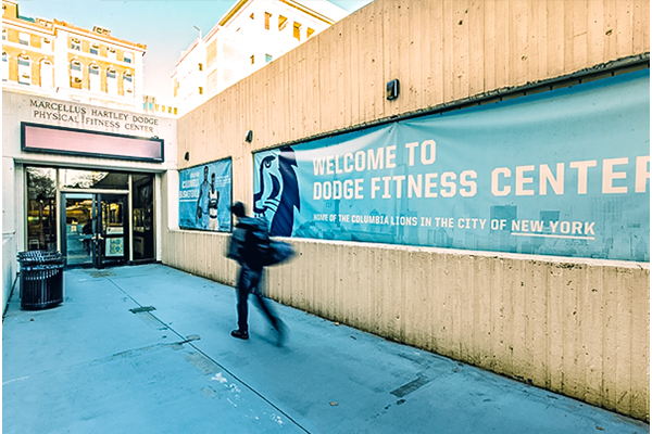 The entrance to the Dodge Fitness Center at Columbia - a student hurries to the entrance with his backpack on his back.